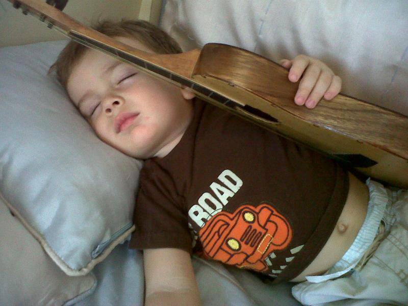 Migue at 2 sleeping with his guitar